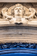 face in stone above an arched doorway in Paris