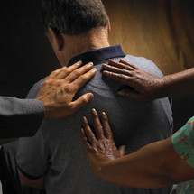 Hands laid on a man's back in prayer.