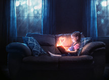 A little girl reading alone with a color heart glowing out of the pages