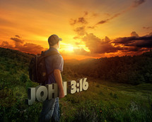 Man in a baseball cap carrying John 3:16 over a hill at sunset.
