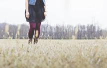 legs of a woman standing in a field