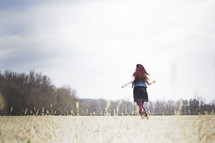 woman running through a field with open arms