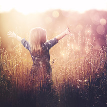 a little girl in a field with open arms