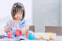 a toddler girl painting with paints