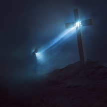 word love on a cross shining down on a man in darkness