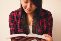 an Asian teen girl reading a bible