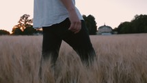 a man walking through a field of tall grasses