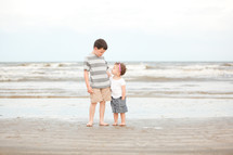 brother and sister standing in the sand on a beach