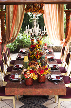 A table setting on a patio fall colors  chandelier