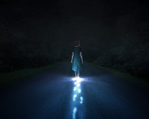 A woman walking down a road a night with glowing footsteps