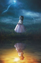 A little girl looking up at a rain storm while her reflection is in warm sunlight