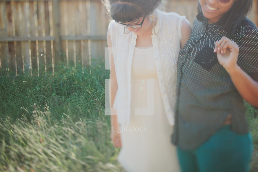 two women waling together smiling