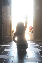 Silhouette of  a girl waving goodbye in a sunlit doorway surrounded by papers on the wood floor.