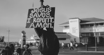 man holding a sign Jesus Saves I repent Amen