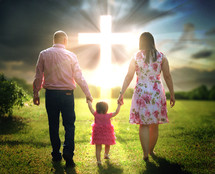 a family holding hands walking together towards a glowing cross in the sky
