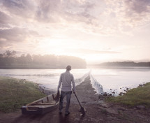 A man with a boat looks at a lake that has the waters parted