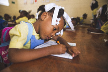 Girl doing her schoolwork on a wooden table.
