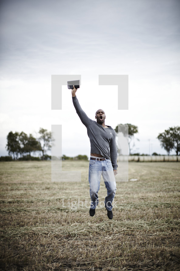 A man jumping in the air with a BIble in hand