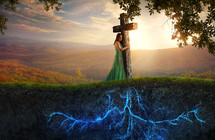 a woman hugging a rooted cross