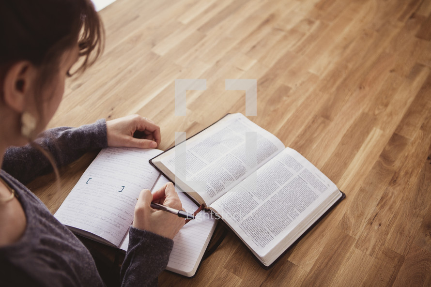 woman writing in a journal and reading a Bible
