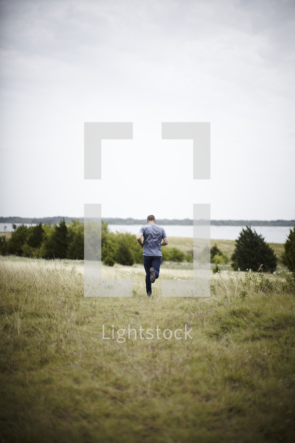 A shot from behind - man running in a field
