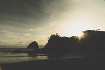 sunburst behind cliffs on a beach at sunset