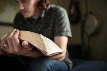 a man reading an oversized Bible