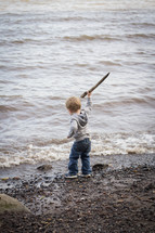 Boy holding a stick on the beach at the ocean.