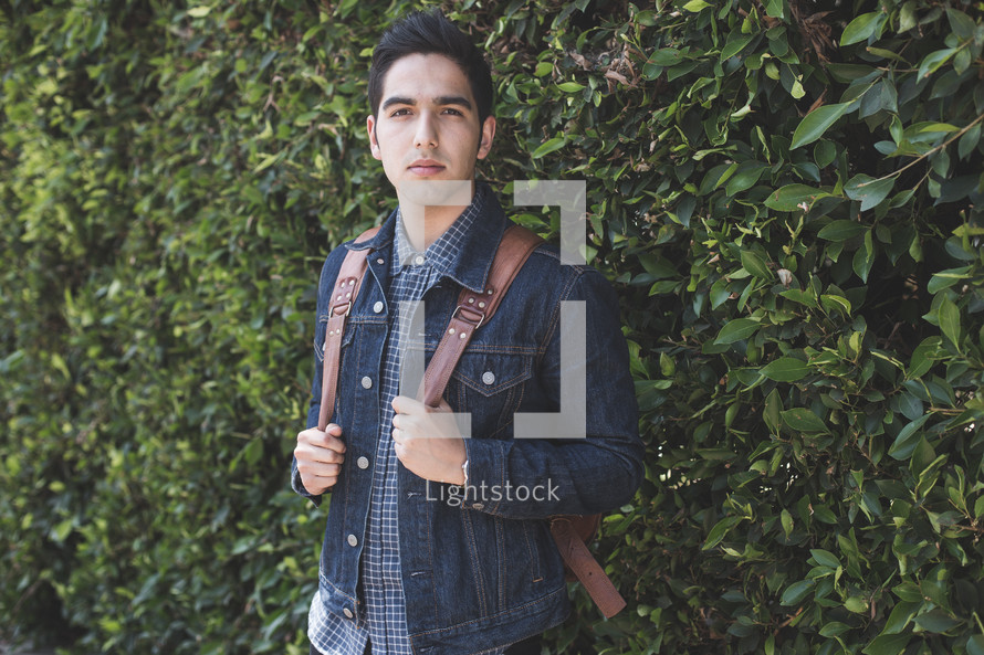 A young man in a backpack standing near a wall of bushes.