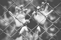 hands on a chain link fence