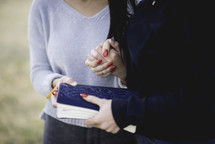 young woman holding a Bible and praying together