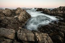 ocean water around rocks on a shore