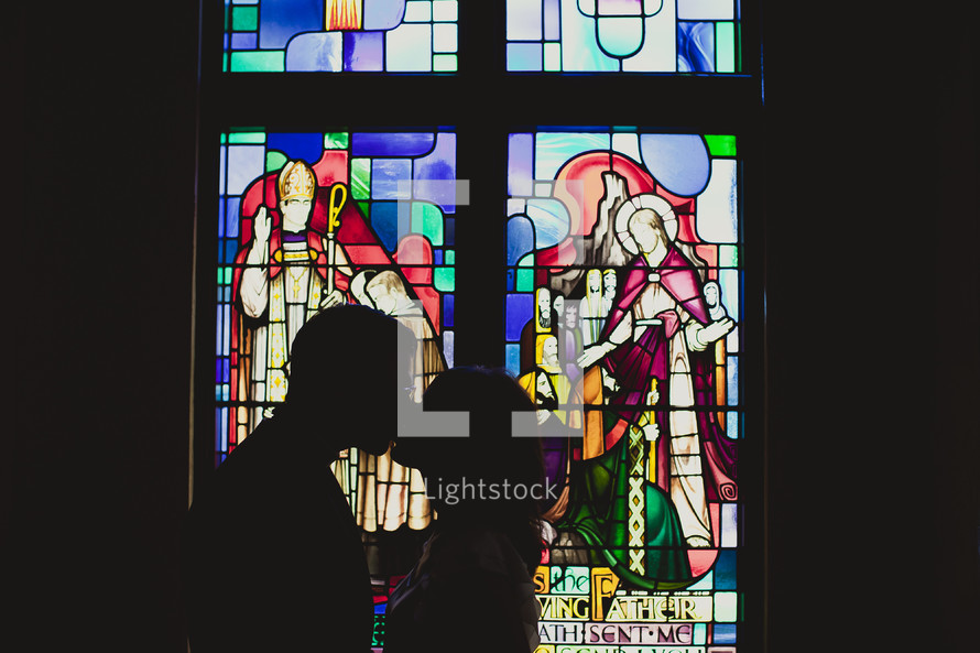 The silhouette of a man and woman kissing in front of a stained glass window