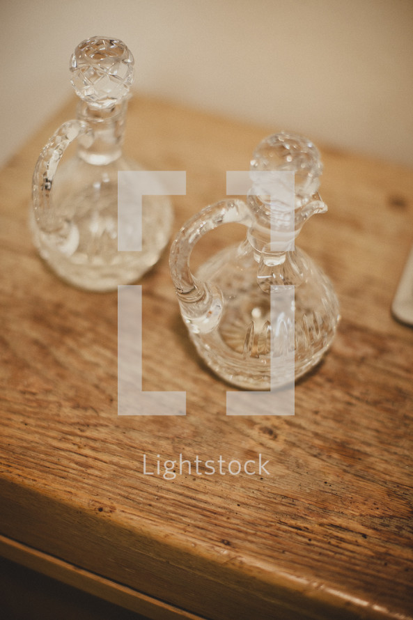 Two glass bottles resting on a wooden table