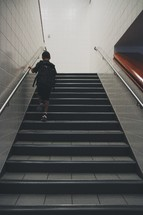 Child with a backpack climbing a flight of stairs.