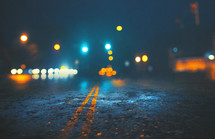 bokeh lights and center lines on a road at night