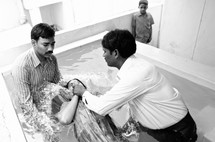 woman being dunked in water during a baptism in India