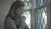 a woman praying at a window