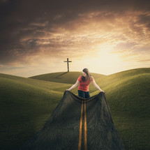 Woman spreading a cloth on the ground that looks like a highway leading to a cross in the distance