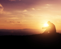 silhouette of a man praying at sunset