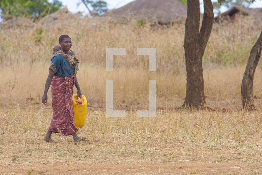 mother carrying a baby on her back carrying a jug of water