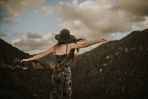a woman on a mountaintop with outstretched arms