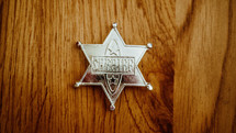toy sheriff badge on a wood floor