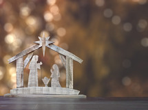 A simple nativity on a table with a bokeh background for adding text.