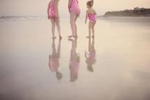 children standing on wet sand at a beach