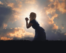a woman kneeling in prayer at sunset