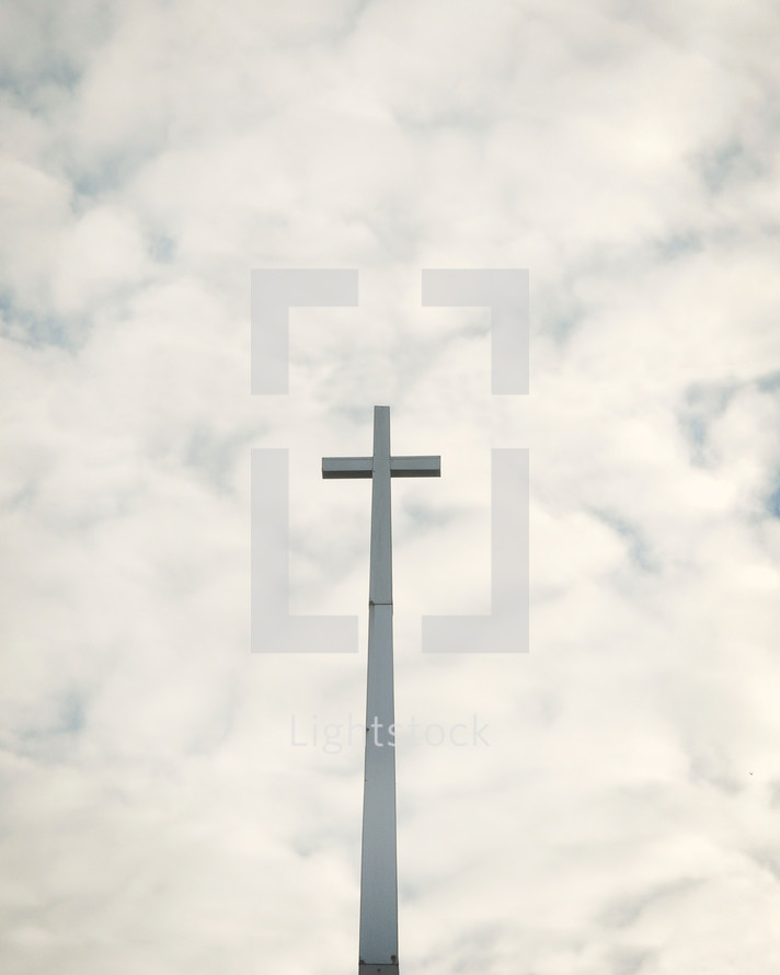 a cross against a cloudy sky