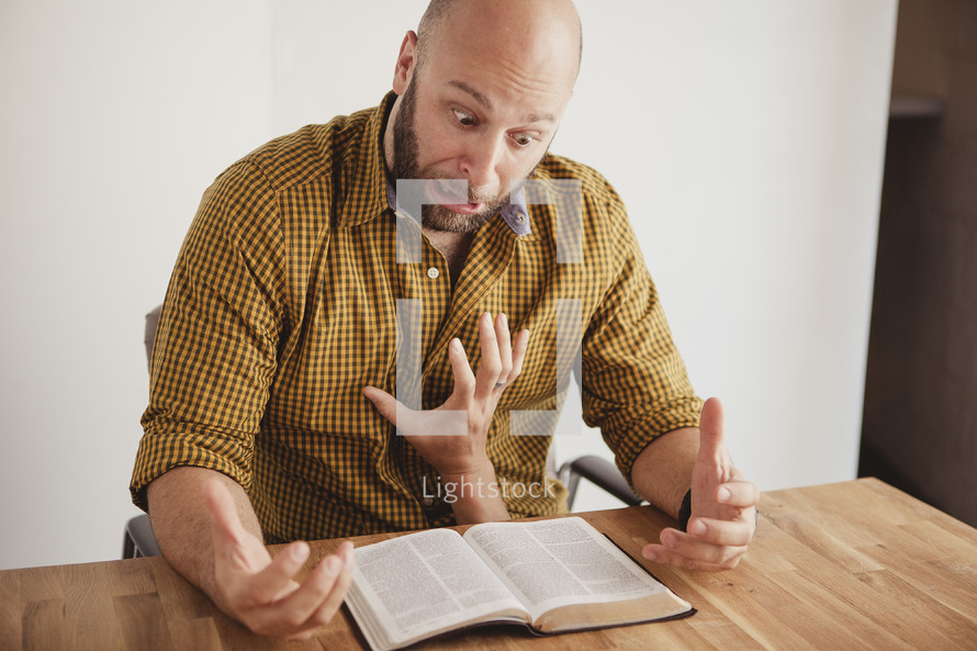 hand grabbing a man who is reading a Bible
