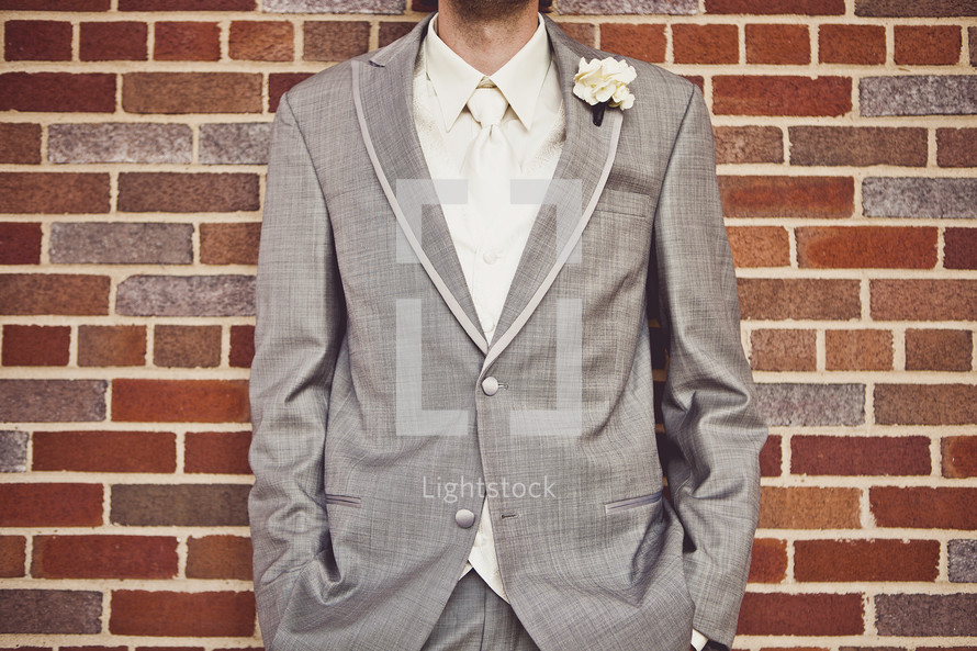 A groom standing in front of a brick wall