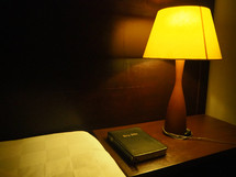 Bible on a wooden night table next to a bed with a lamp on it.